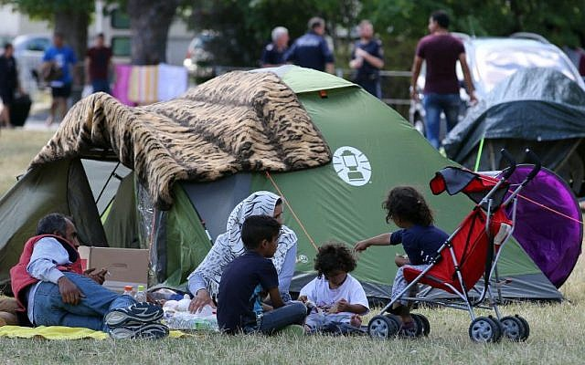 Illustrative: Refugees wait outside the refugee camp in Traiskirchen, Austria, Friday, July 31, 2015. (AP Photo/Ronald Zak)