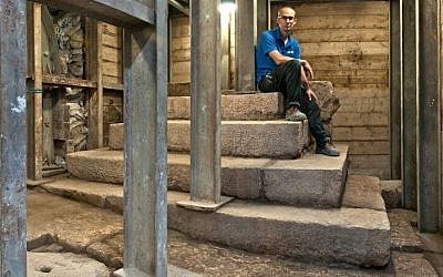 Joe Uziel, co-director of an Israel Antiques Authority excavation, sitting atop the stepped structure from the Second Temple period in Jerusalem. (Shai Halevy/ Israel Antiquities Authority)