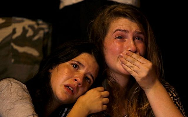 Israeli girls cry during a gathering of hundreds of friends, classmates, teachers, members of the LGBT community and supporters in downtown Jerusalem on August 2, 2015 to mourn the death of Shira Banki (AFP/GALI TIBBON)