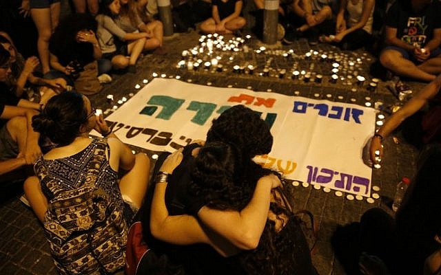 People gather around candles during a gathering of hundreds of friends, classmates, teachers, members of the LGBT community and supporters in downtown Jerusalem on August 2, 2015 to mourn the death of Israeli Shira Banki (AFP  GALI TIBBON)