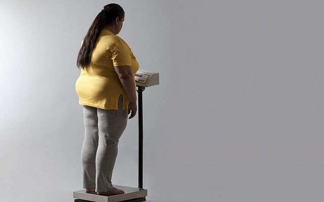 Illustrative photo of an obese woman on a scale. (Photo via Shutterstock)