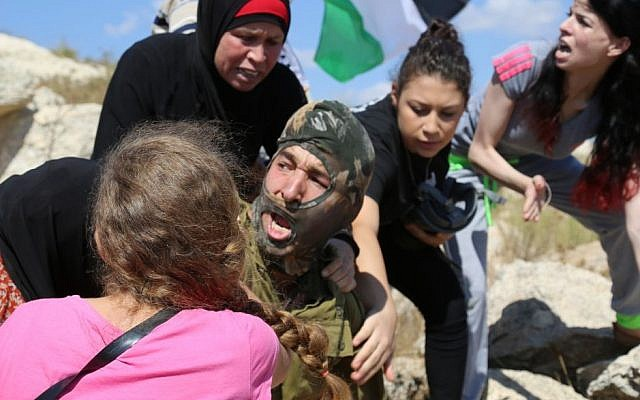 Palestinians  fight to stop an IDF soldier from arresting a 12-year-old boy with a broken arm in a cast accused of throwing stones (Eric Cortellessa/Times of Israel)