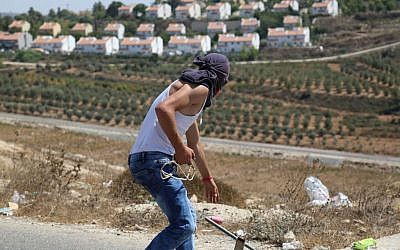 Illustrative: A Palestinian prepares to throw stones at IDF soldiers guarding the Halamish settlement. (Eric Cortellessa/Times of Israel)