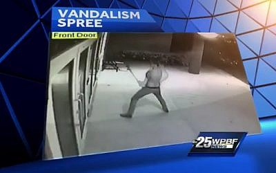 A man is caught on surveillance camera smashing the glass doors of a South Florida synagogue. (screen capture: WPBF-TV)