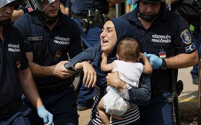A migrant family is arrested by local police after their local train coming from Budapest and heading to the Austrian border has been stopped in Bicske, west of the Hungarian capital on September 3, 2015. (AFP PHOTO / ISTVAN BIELIK)