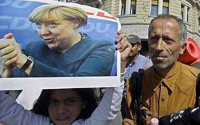 A migrant girl holds a poster of German Chancellor Angela Merkel as migrants walk in Budapest downtown after leaving the transit zone of the main train station, on September 4, 2015 intent on walking to the Austrian border.  (AFP PHOTO / PETER KOHALMI)