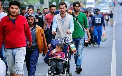 A migrant group walks down the No.1 main road near Budaors, Hungary on September 5, 2015 to head to the Hungarian-Austrian border. (AFP/ATTILA KISBENEDEK)