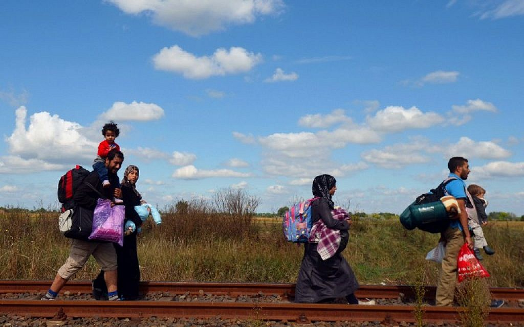 Migrant families walk at the railway track at the Hungarian-Serbian border near Roszke village on September 6, 2015. (AFP/CSABA SEGESVARI)