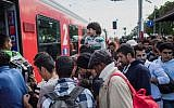 Illustrative: Migrants enter a train heading to Salzburg at Nickelsdorf, eastern Austria, on September 6, 2015. (AFP/VLADIMIR SIMICEK)