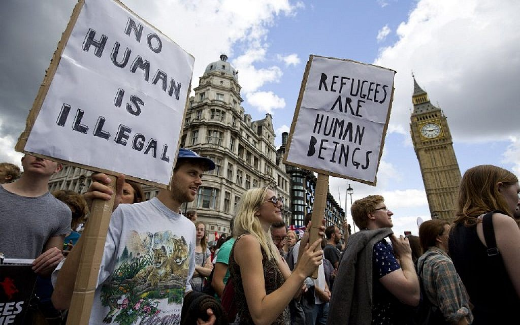 Demonstrators hold placards as pass the Houses of Parliament during a pro-refugee rally in central London on September 12, 2015. (AFP PHOTO / JUSTIN TALLIS)