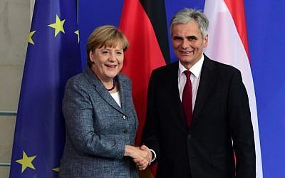 German Chancellor Angela Merkel and her Austrian counterpart Werner Faymann shake hands following a press conference at the Chancellery in Berlin on September 15, 2015, after their meeting on the refugee crisis. (AFP PHOTO / JOHN MACDOUGALL)