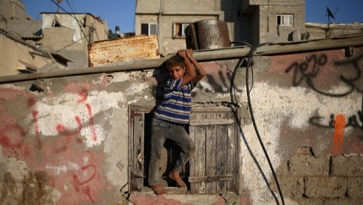 A Palestinian child plays next to his house at the Al-Shatee refugee camp in Gaza City on August 27, 2015. (AFP/ MOHAMMED ABED)