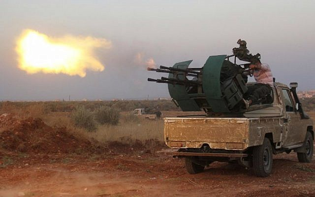 Rebel fighters fire a heavy machine gun during clashes with Syrian pro-government forces on the front facing Deir al-Zoghb, a government-held area in the northwestern Idlib province, on August 31, 2015. (AFP Photo/Omar Haj Kadour)