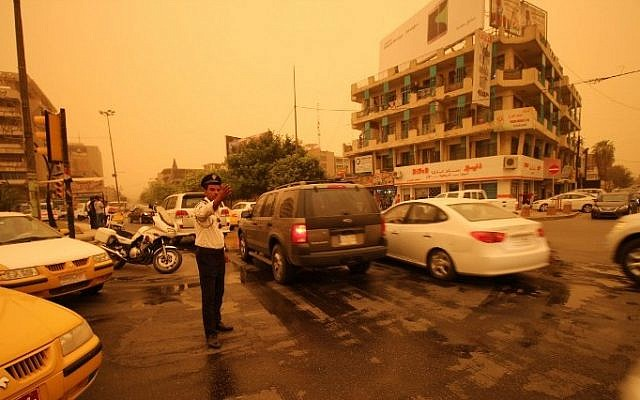An Iraqi policeman organizes traffic on a street in Baghdad during a sandstorm on September 1, 2015.  (AFP/HAIDAR MOHAMMED ALI)