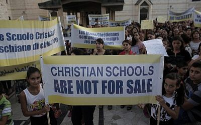 Hundreds of Israeli Christians hold banners in a rally against what they said was state discrimination in funding their schools, at the foot of the Basilica of the Annunciation in Nazareth on September 1, 2015 (Ahmad Gharabli/AFP)