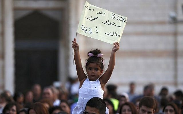 An Arab-Israeli Christian child holds a banner during a rally against alleged state discrimination in funding of Christian schools at the foot of the Basilica of the Annunciation in Nazareth on September 1, 2015. (AFP/AHMAD GHARABLI)