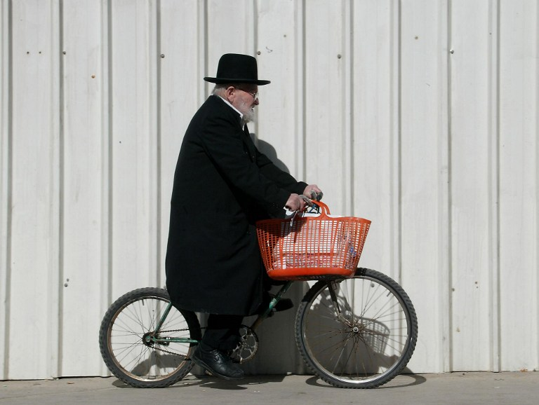 A picture dated on February 5, 2002 shows an ultra-Orthodox Jewish man riding his bicycle with his shopping basket hanging on the handles as he makes his way to the outdoors market in Jerusalem. (AFP/Gabriel BOUYS)