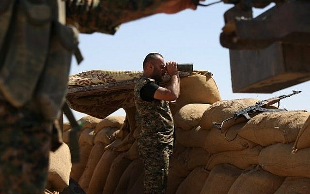 File: A fighter from the Kurdish People Protection Unit (YPG) uses binoculars on the front line in the northeastern Syrian city of Hasakeh on September 4, 2015. (Delil Souleiman/AFP)