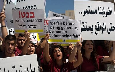 Arab Israeli Christian students hold placards during a protest in Jerusalem to demand more funds for Christian schools, on September 6, 2015. (AFP/Menahem Kahana)