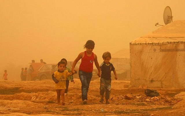Syrian children walk amid the dust during a sandstorm on September 7, 2015 at a refugee camp on the outskirts of the eastern Lebanese city of Baalbek. (AFP Photo/STR)