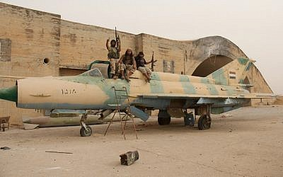 Members of Al-Qaeda's Syrian affiliate and its allies sit on top of a Russian-made former Syrian army fighter jet after they seized the Abu Duhur military airport, the last regime-held military base in northwestern Idlib province on September 9, 2015 (AFP/OMAR HAJ KADOUR)
