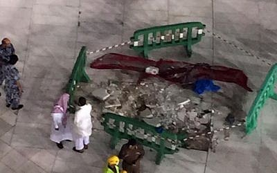 Saudi emergency teams gather inside the Grand Mosque of Saudi Arabia's holy Muslim city of Mecca next to a piece of a construction crane after it crashed into the mosque on September 11, 2015, killing more than 100 people. (AFP PHOTO/STR)