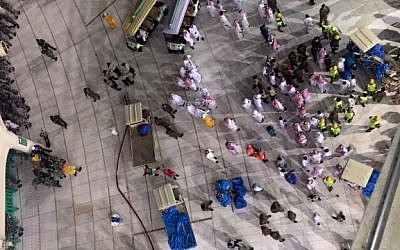 Saudi emergency teams gather inside the Grand Mosque of Saudi Arabia's holy Muslim city of Mecca after a construction crane crashed into it on September 11, 2015, killing dozens of people. (AFP PHOTO/STR)
