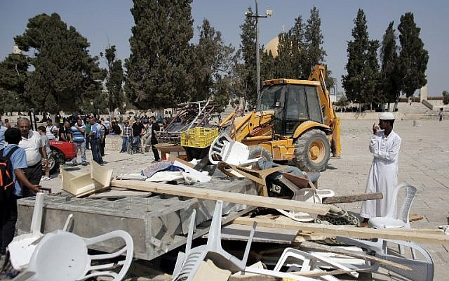 Palestinians clear the damage at the entrance of al-Aqsa Mosque in Jerusalem following clashes with Israeli riot police on September 15, 2015. (AFP PHOTO/AHMAD GHARABLI)