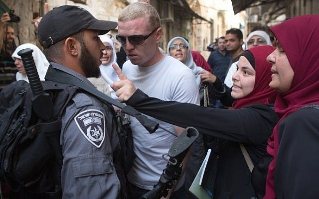 Palestinian women argue with Israeli policemen during a protest against Jewish groups visiting the Temple Mount, which houses Al-Aqsa Mosque in Jerusalem, on September 16, 2015. (AFP/Menahem Kahana)