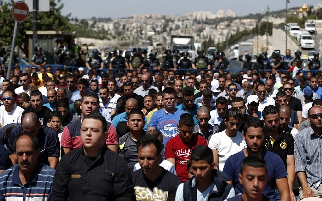 Israeli security forces stand guard as Palestinian Muslim worshipers take part in Friday noon prayers in the East Jerusalem neighborhood of Ras al-Amud on September 18, 2015, (AFP PHOTO/AHMAD GHARABLI)