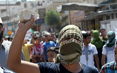 Illustrative: A Palestinian protester in Hebron holds a stone during clashes with Israeli security forces following an anti-Israeli protest after the weekly Friday prayers on September 18, 2015. AFP  PHOTO / HAZEM BADER