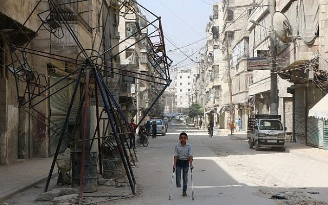 Illustrative: Osama, a fourteen-year-old boy who lost his foot in an air strike led by Syrian government forces, walks on a street in the rebel-held side of the nothern city of Aleppo on September 19, 2015. (Baraa al-Halabi/AFP)