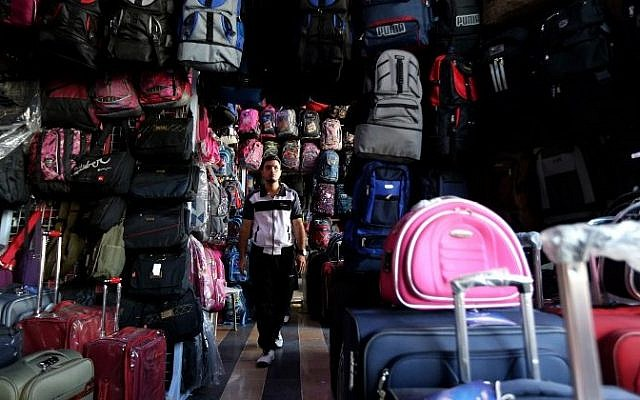 A Syrian man looks at backpacks and suitcases for sale at a market in Damascus on September 22, 2015. When customers ask which of the backpacks displayed in the Souk al-Khija market is the sturdiest, the shopkeeper knows they are planning to take to the sea to reach Germany. (AFP/LOUAI BESHARA)