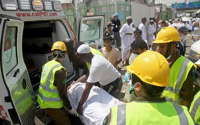 Saudi emergency personnel and Hajj pilgrims load a wounded person into an ambulance at the site where at least 450 were killed and hundreds wounded in a stampede in Mina, near the holy city of Mecca, at the annual hajj in Saudi Arabia on September 24, 2015.(AFP PHOTO / STR)