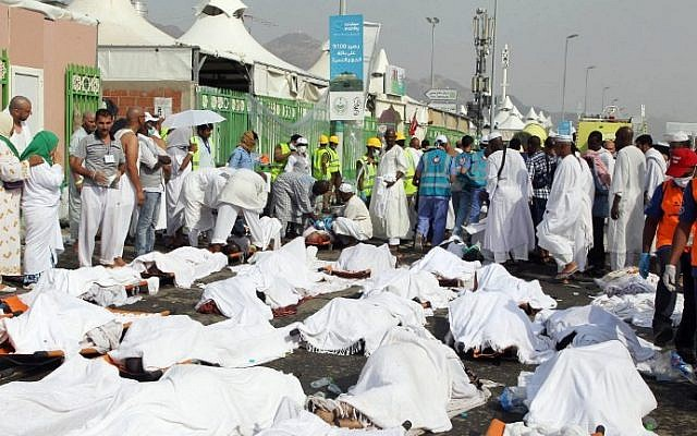 Saudi emergency personnel stand near bodies of Hajj pilgrims at the site where at least 717 were killed and hundreds wounded in a stampede in Mina, near the city of Mecca, at the annual hajj in Saudi Arabia on September 24, 2015. (STR/AFP)