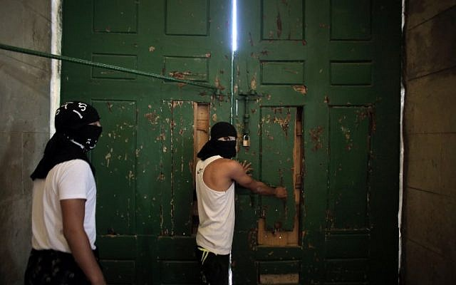 Masked Palestinians secure the door of Jerusalem's Al-Aqsa Mosque, one of Islam's holiest sites, on September 27, 2015. (AFP PHOTO/AHMAD GHARABLI)