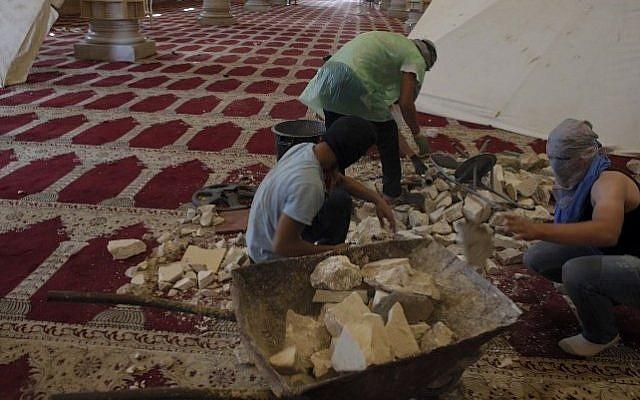 Masked Palestinians prepare stones inside Jerusalem's Al-Aqsa Mosque, one of Islam's holiest sites, on September 27, 2015. (AFP PHOTO/AHMAD GHARABLI)