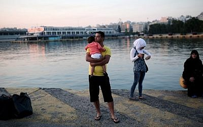 A migrant holds his child as he arrived with his family at the port of Piraeus near Athens on June 14, 2015. (Angelos Tzortzinis/AFP)