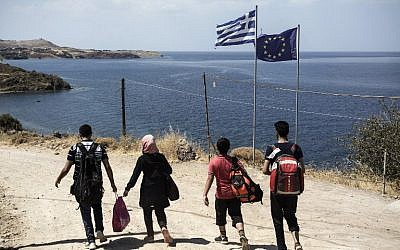 Syrian migrants walk past Greek and European flags as they head towards the town of Mithimna on Lesbos island, after arriving in an inflatable boat from Turkey on August 22, 2015. (AFP PHOTO / ACHILLEAS ZAVALLIS)