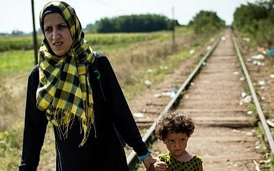 A migrant woman with her daughter walk down a railroad track towards the Hungarian border near the northern Serbian town of Horgos on August 27, 2015. (AFP PHOTO / ANDREJ ISAKOVIC)