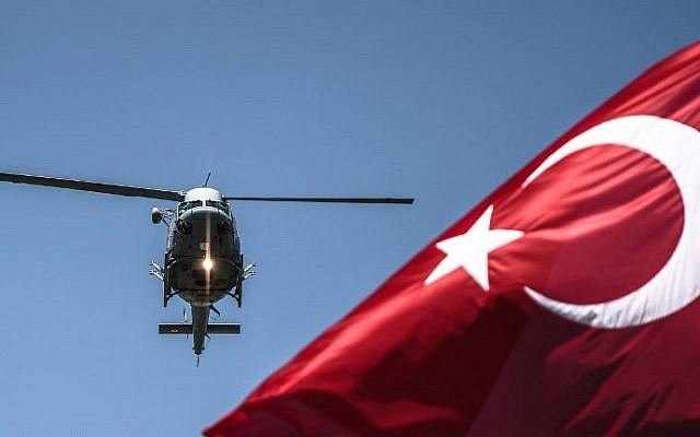 A Turkish army helicopter flies behind a Turkish flag during a military parade marking the 93rd anniversary of Victory Day in Istanbul on August 30, 2015. (Ozan Kose/AFP)