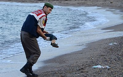 A Turkish police officer carries a migrant child's dead body off the shores in Bodrum, southern Turkey, on September 2, 2015 after a boat carrying refugees sank. (AFP/DOGAN NEWS AGENCY)