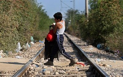 A migrant child crosses the Greek-Macedonian border near the vilage of Idomeni, northern Greece, on September 4, 2015. (AFP/Sakis Mitrolidis)