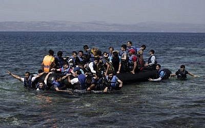Syrian refugees arrive on the shores of the Greek island of Lesbos after crossing the Aegean Sea from Turkey on a inflatable dinghy, September 11, 2015. (AFP/ANGELOS TZORTZINIS)