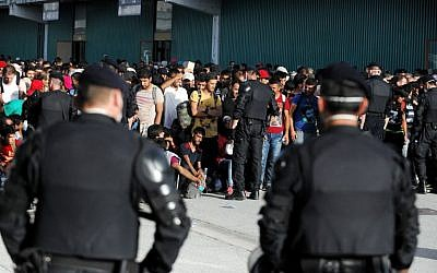 Croatian police stand guard as migrants and refugees gather in Zagreb's Fair Convention center,  on September 18, 2015. (AFP PHOTO/STR)
