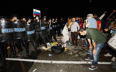 Migrants react after pepper spray was used in a small village of Rigonce in Slovenia, a small border crossing point to Harmica, Croatia, on September 18, 2015.   (AFP / JURE MAKOVEC)