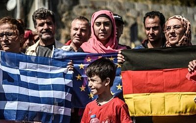 A young migrant stands in front of European Union flags as migrants and refugees stage a demonstration at Istanbul's Esenler Bus Terminal,  September 19, 2015. (AFP Photo/Ozan Kose)