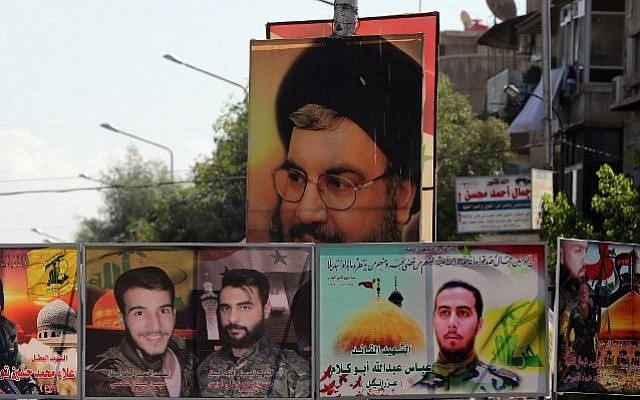 File: A file picture taken on September 21, 2015 shows a portrait of Hassan Nasrallah (top), the head of Lebanon's militant Shiite Muslim movement Hezbollah, and portraits of pro-government force members killed in combat displayed on a street in the Syrian capital, Damascus. (AFP PHOTO/JOSEPH EID)