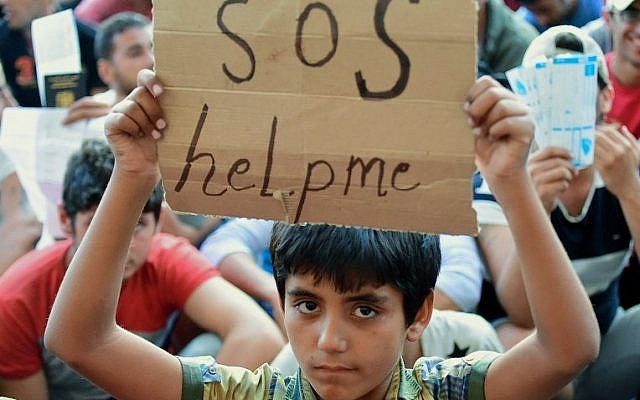A migrant boy holds a sign reading 'SOS help me' as he sits with other migrants in front of the Keleti (East) railway station in Budapest on September 2, 2015. (AFP PHOTO / ATTILA KISBENEDEK)