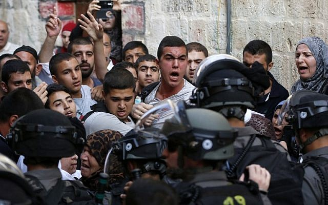 Palestinians shout in front of Israeli security forces who block a road leading to the Al-Aqsa mosque compound in Jerusalem's Old City on September 13, 2015. (AFP PHOTO / AHMAD GHARABLI)